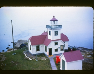 "Coast Guard Officer-in-Charge Dale Nelson climbed on the flagpole to take this wonderful picture of the lighthouse, late ""50s."